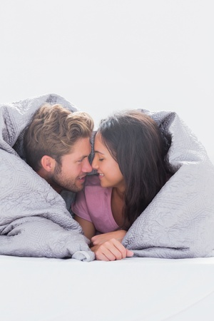 Beautiful couple wrapped in the duvet in bed photo