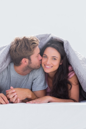Man kissing his wife under the duvet in their bed photo