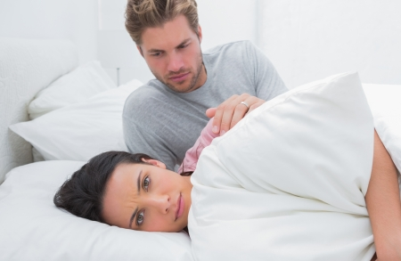 Sad woman ignoring her partner in her bed during a conflict photo
