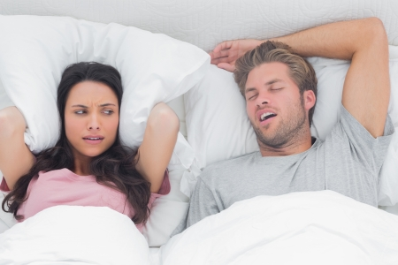 snoring: Pretty woman annoyed by the snoring of her husband in bed