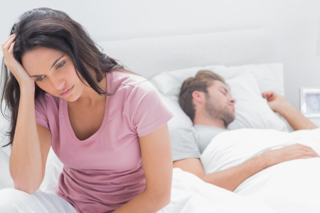 Anxious woman thinking in her bed next to her sleeping partner photo
