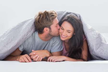 pareja en la cama: Atractivo hombre besando a su esposa bajo el edred�n en la cama