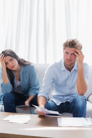 Anxious couple doing their accounts in the living room photo