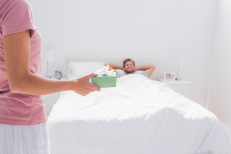 Woman offering a present to her husband in bed Stock Photo - 20618803