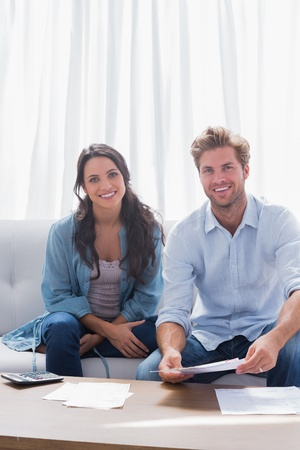 Couple smiling while doing their accounts sat in a couch Stock Photo - 20637654