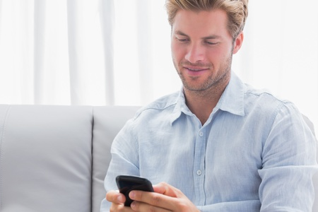 Man using his phone on a couch in the living room photo