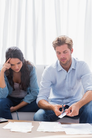 Worried couple doing their accounts together sat in a couch Stock Photo - 20637725