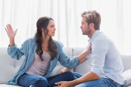 slap: Angry woman about to slap her partner in living room Stock Photo
