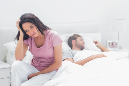 couple bed: Anxious woman thinking while she is sat in her bed next to her sleeping partner