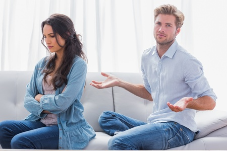 gesturing: Woman with arms crossed back to her partner who is gesturing Stock Photo