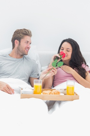 Woman smelling a rose given by her husband in their bed during breakfast photo