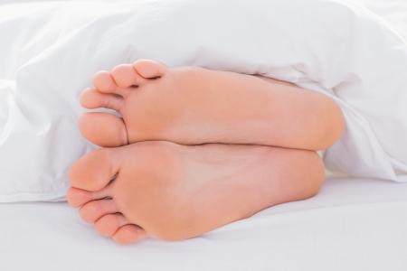 Füße in einem Bett unter der Bettdecke