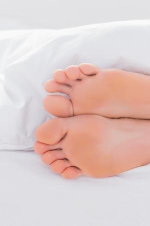 Feet under a duvet in a bed photo