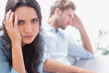 restless: Upset woman holding her head next to her partner