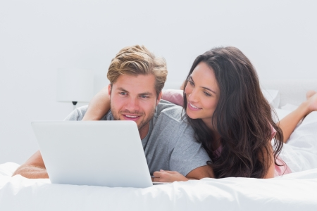 Woman embracing husband while using a laptop in bed photo
