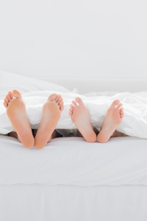 Feet of lovers under the duvet in their bed photo