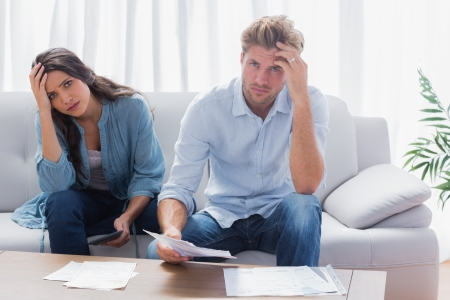 Stressed paar dat hun rekeningen in de woonkamer