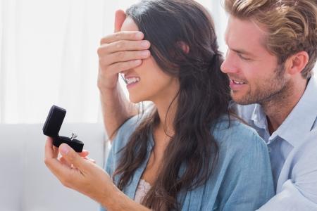 彼女に結婚のプロポーズのための婚約指輪を提供する彼の wifes の目を隠れている男