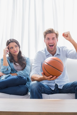 Woman looking at her husband cheering the basketball game at home on couch photo