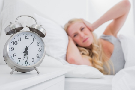 Tired woman covering ears with hands while the alarm clock is ringing Stock Photo - 20618975