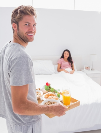 Man bringing breakfast to his wife at bed photo