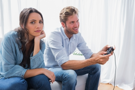 Upset woman annoyed that her partner is playing video games at home on the couch photo