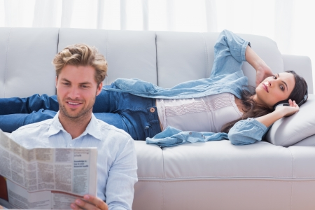 Woman relaxing on a couch listening to music next to her partner reading a newspaper photo
