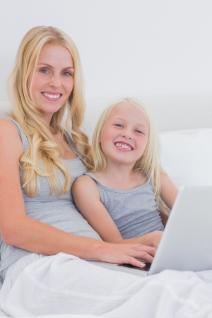 Mother and daughter using a laptop in bed photo