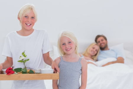 Happy children bringing breakfast in bed to their parents Stock Photo - 20635176