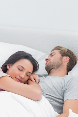 Pretty woman sleeping on her husbands chest in bed photo