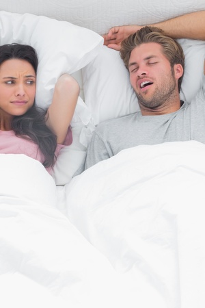 Brunette annoyed by the snoring of her husband next to her photo