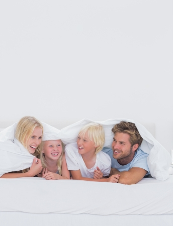 Cheerful family under the duvet at home in bed photo