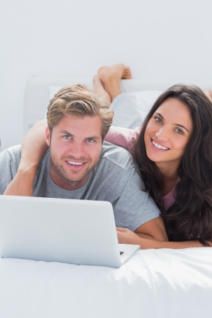 Happy woman embracing husband while using a laptop in bed photo