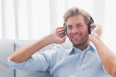Man listening to music with headphones in the couch in the living room photo