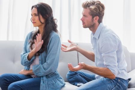 personne en colere: Femme faisant des gestes tout en se querellant avec son partenaire dans le salon