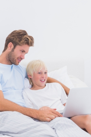 Father and his son using a laptop in bed photo