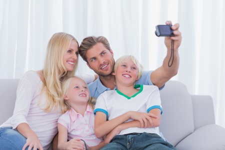 Family taking pictures of themselves in the living room photo