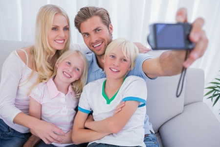 Family taking pictures of themselves in living room photo