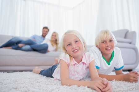 Children lying on the carpet and smiling at camera photo