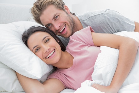 Couple laughing and looking at camera in bed photo