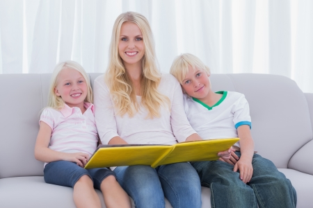 Portrait of a mother holding a story book with children on couch photo
