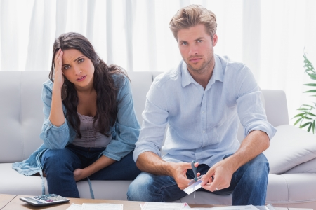 Couple looking anxious while doing their accounts together in the living room photo