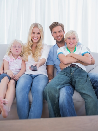 Parents and children watching TV in the living room photo