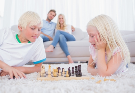 Cute siblings playing chess on the carpet Stock Photo - 20634684