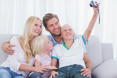 Little boy taking pictures of his family in the living room photo