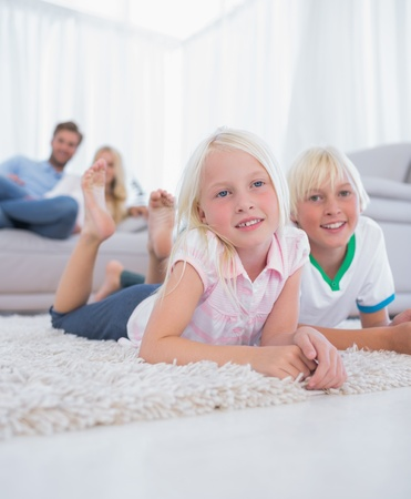 Cute children lying on the carpet smiling at camera in the living room photo