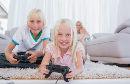 Siblings playing video games in the living room photo