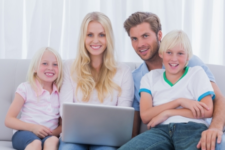 Cheerful family using a laptop sat on the couch photo