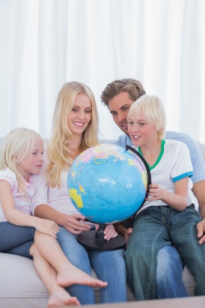 Happy family looking at globe on couch in living room photo