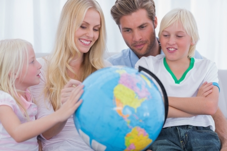 Smiling family with globe in sitting room photo